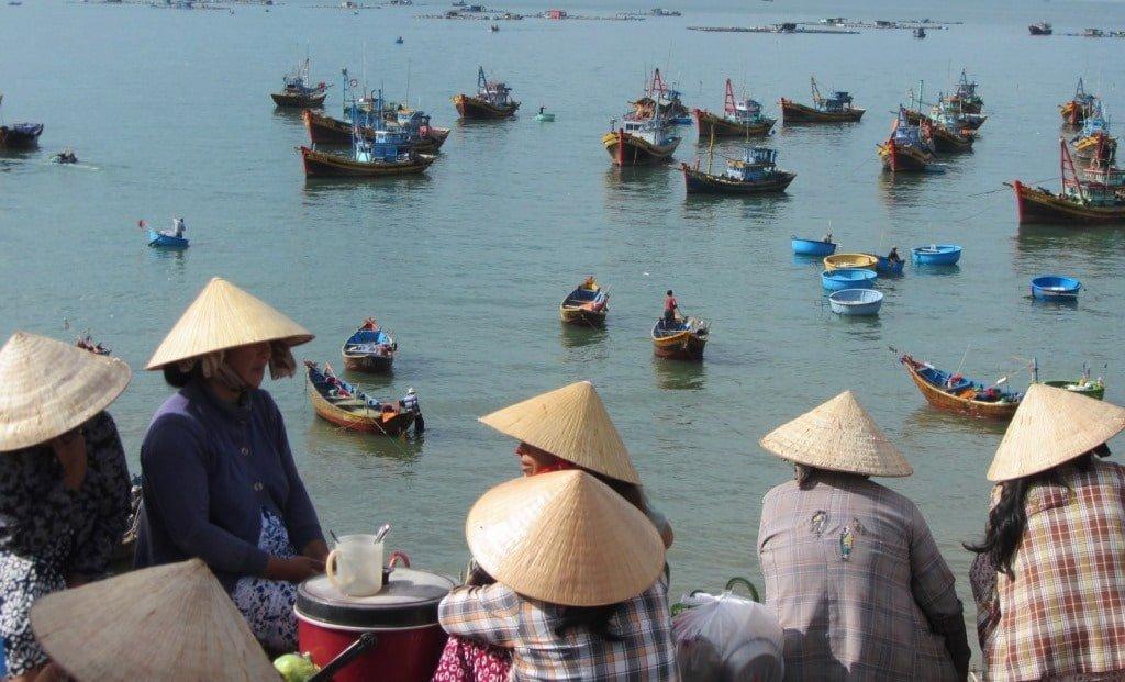 Women gather at dawn to meet the fishing boats, Mui Ne
