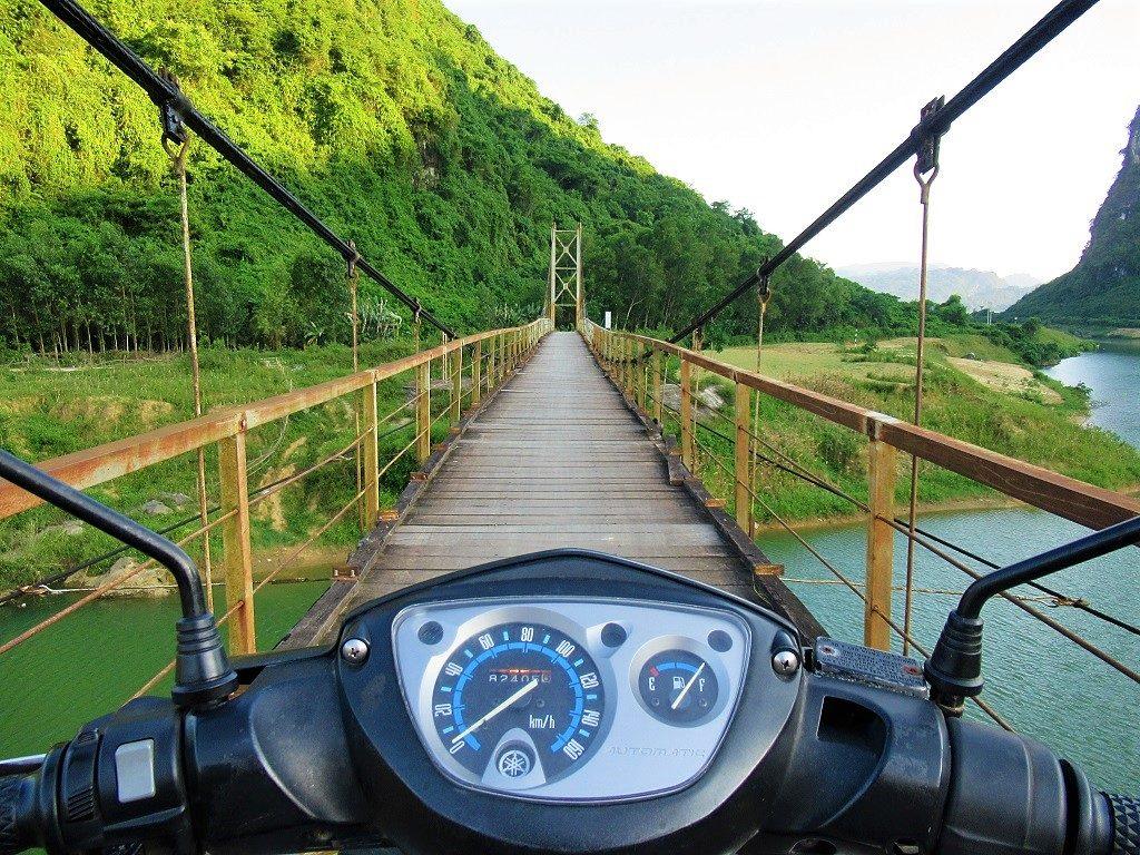 Riding over a suspension bridge, Phong Nha, Vietnam