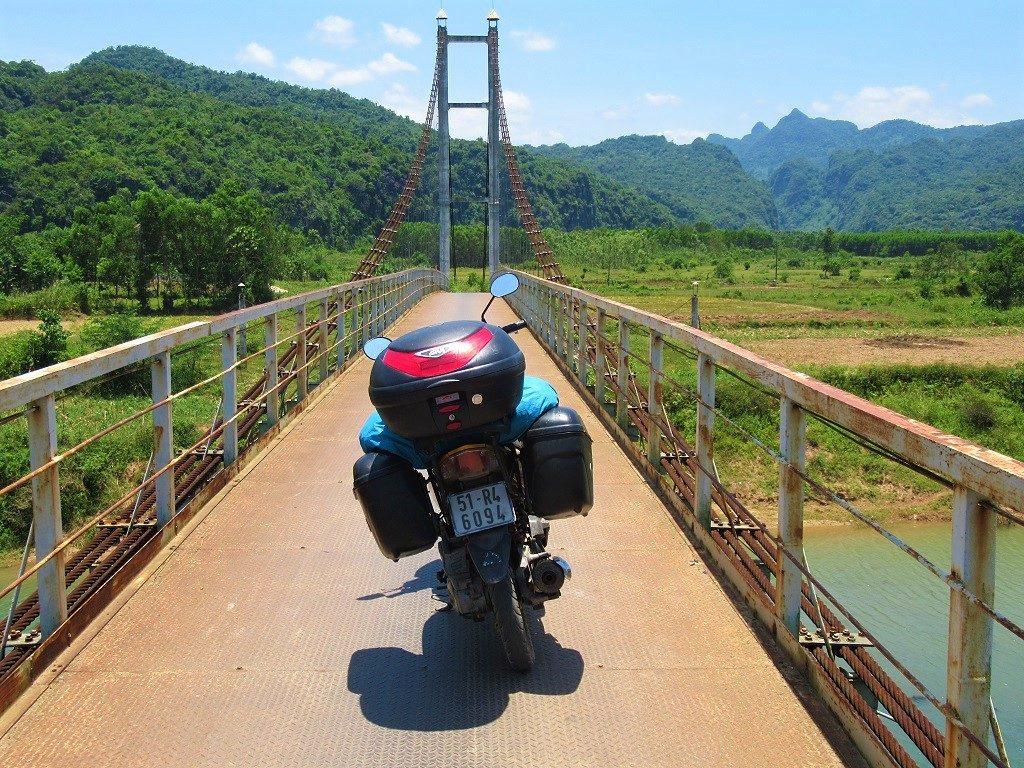 Riding across a suspension bridge, Phong Nha, Vietnam